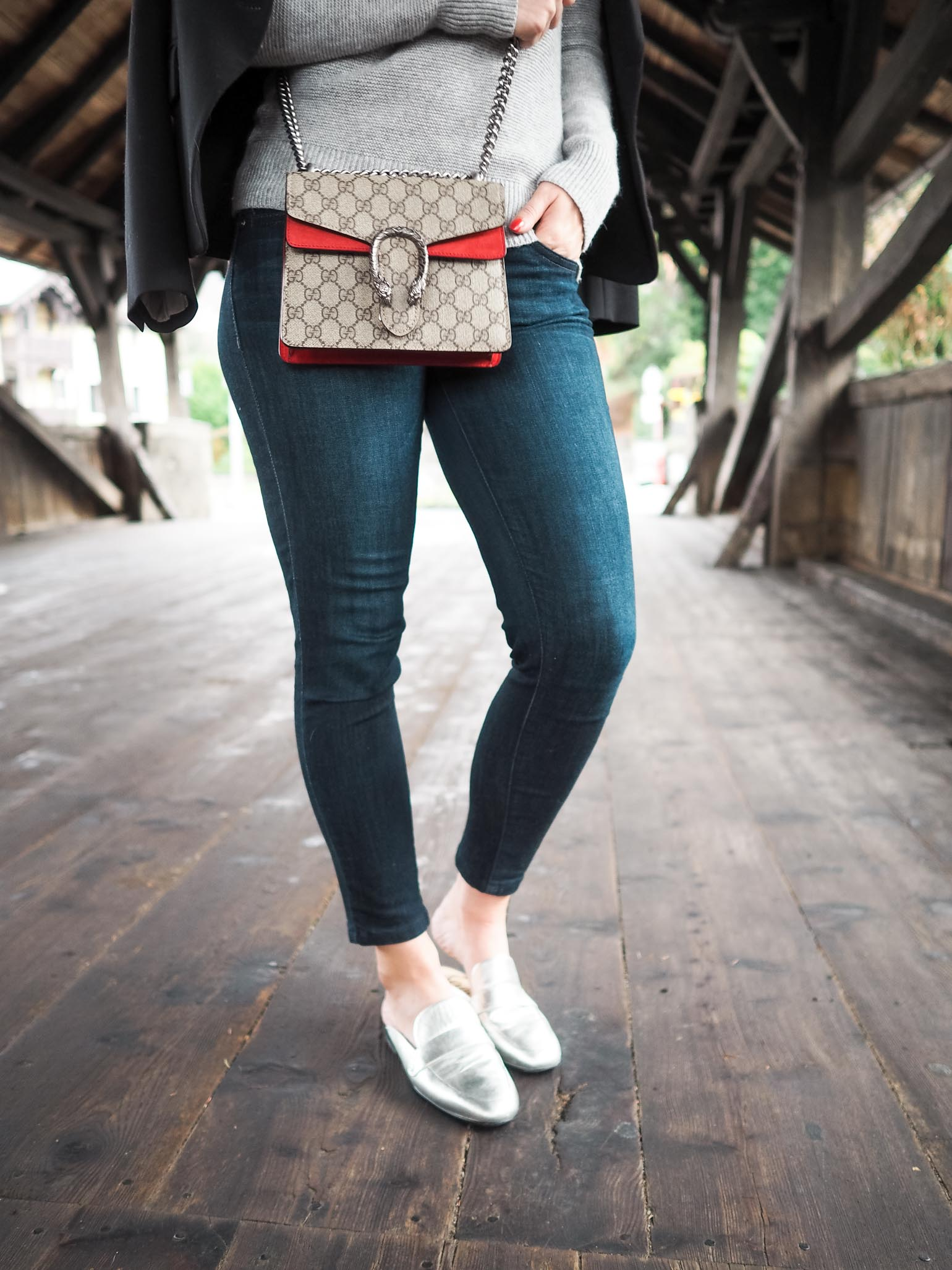 Cristina from The Brunette Nomad, a Dallas fashion blogger living in Switzerland, is styling a tone on tone look with a grey Banana Republic sweater and silver metallic Sam Edelman mules
